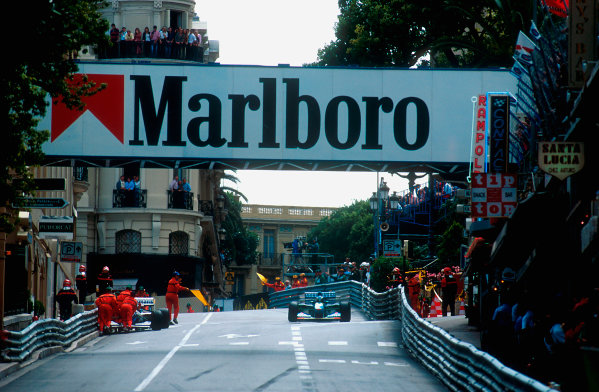 1994 Monaco Grand Prix.Monte Carlo, Monaco.12-15 May 1994.Michael Schumacher (Benetton B194 Ford) 1st position passes marshals who are moving Hill's broken Williams.Ref-94 MON 51.World Copyright - LAT Photographic