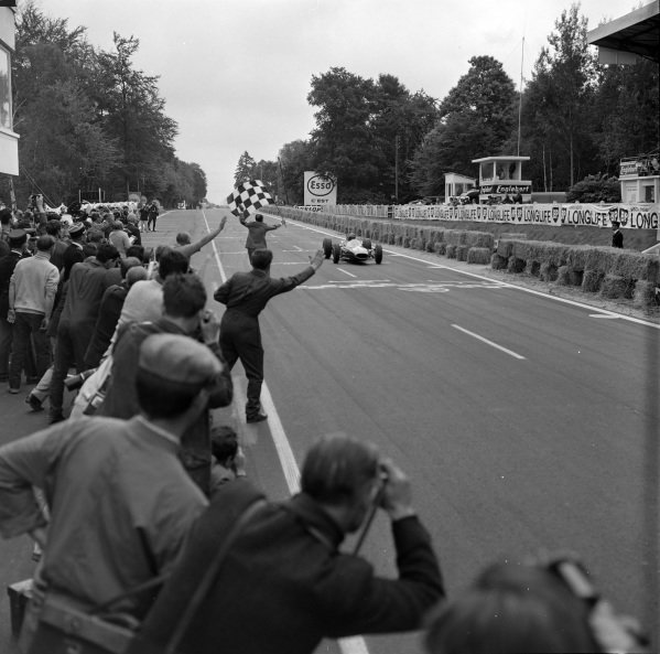 Dan Gurney, Brabham BT7 Climax, crosses the finish line and takes the chequered flag.