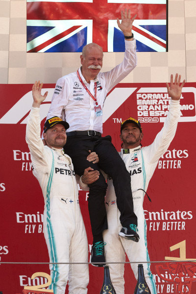 Valtteri Bottas, Mercedes AMG F1, 2nd position, and Lewis Hamilton, Mercedes AMG F1, 1st position, lifts Dr Dieter Zetsche, CEO, Mercedes Benz, onto their shoulders on the podium
