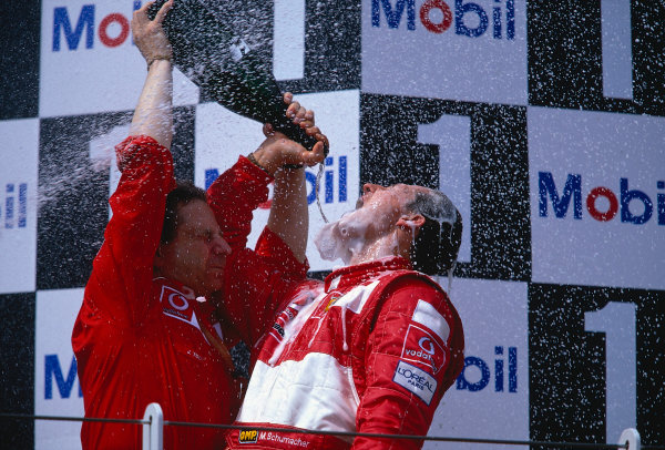 2002 French Grand Prix.Magny-Cours, France. 19-21 April 2002.Michael Schumacher (Ferrari) celebrates his 1st position and record equalling 5th formula one drivers World Championship with Team Principal Jean Todt on the podium.Ref-02 FRA 40.World Copyright - LAT Photographic