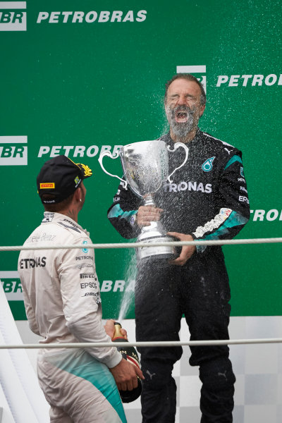 Interlagos, Sao Paulo, Brazil. Sunday 15 November 2015. Lewis Hamilton, Mercedes AMG, 2nd Position, sprays James Waddell, Composite Technician, Mercedes AMG F1, with Champagne. World Copyright: Steve Etherington/LAT Photographic ref: Digital Image SNE13028