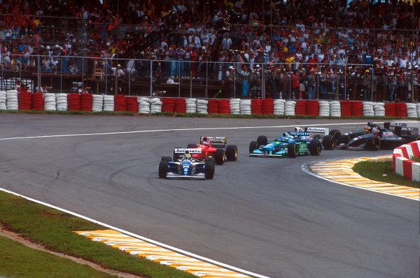 Interlagos, Sao Paulo, Brazil.25-27 March 1994.Ayrton Senna (Williams FW16 Renault) leads Jean Alesi (Ferrari 412T1), Michael Schumacher (Benetton B194 Ford), Damon Hill (Williams FW16 Renault), Heinz-Harald Frentzen and Karl Wendlinger (both Sauber C13 Mercedes) out of the first corner at the start.Ref-94 BRA 10.World Copyright - LAT Photographic
