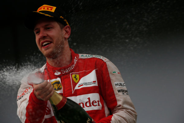 Sepang International Circuit, Sepang, Kuala Lumpur, Malaysia. Sunday 29 March 2015. Sebastian Vettel, Ferrari, 1st Position, celebrates on the podium. World Copyright: Andrew Hone/LAT Photographic. ref: Digital Image _ONZ0577