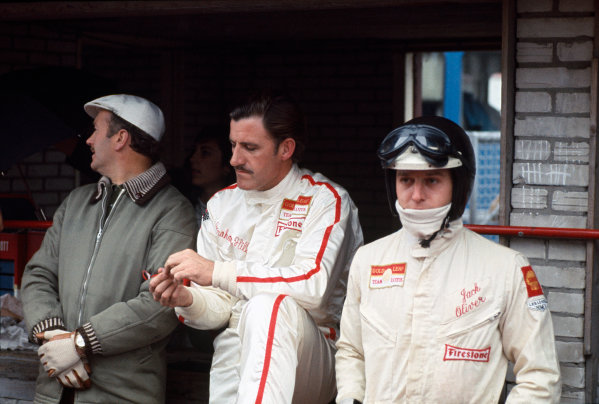 Team Lotus boss Colin Chapman with drivers, Graham Hill and Jackie Oliver in the pits, portrait.World Copyright: LAT Photographic.Ref: Colour Transparency.