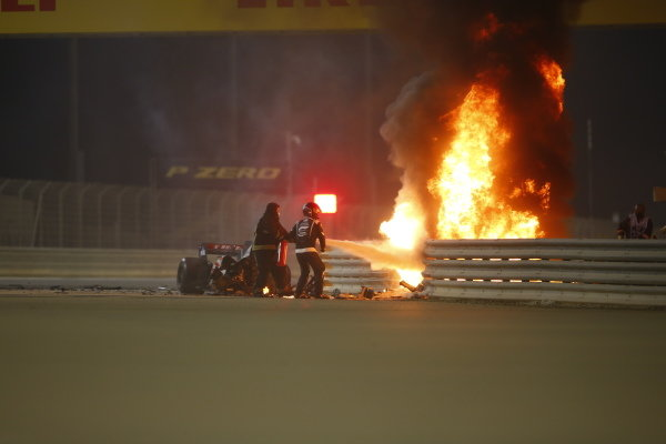 Marshals attend to the flames after a huge crash for Romain Grosjean, Haas VF-20, on the opening lap