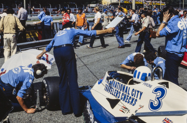 Tyre checks are performed on Didier Pironi's Tyrrell 008 Ford.