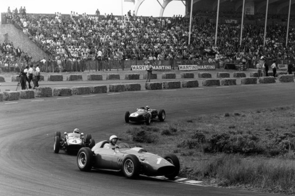 1960 Dutch Grand Prix Zandvoort, Holland. 6 June 1960 Phil Hill, Ferrari Dino 246, retired, leads Innes Ireland, Lotus 18-Climax, 2nd position, and Alan Stacey, Lotus 18-Climax, retired, action World Copyright: LAT PhotographicRef: Autosport b&w print. Published: Autosport, 10/6/1960 p793