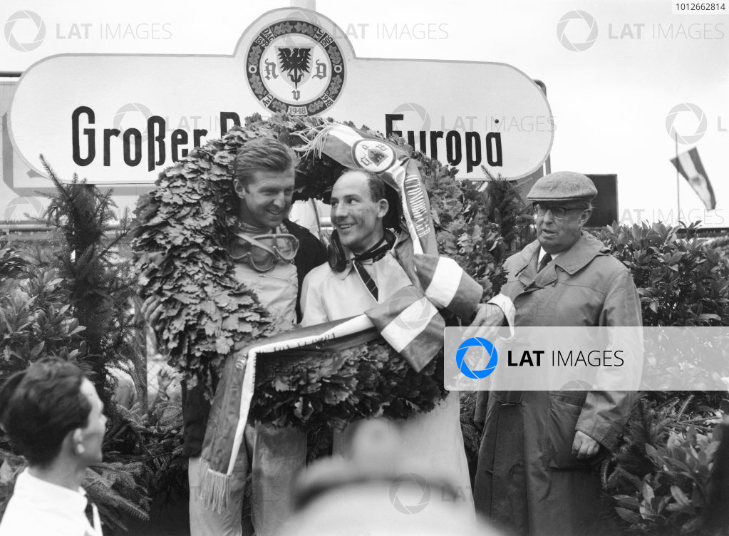 Nurburgring, Germany. 6th August 1961.Wolfgang von Trips (Ferrari Dino 156) and Stirling Moss (Lotus 18/21-Climax) celebrate on the podium, portrait.World Copyright: LAT Photographic.Ref : Autocar Glass Plate C63185.