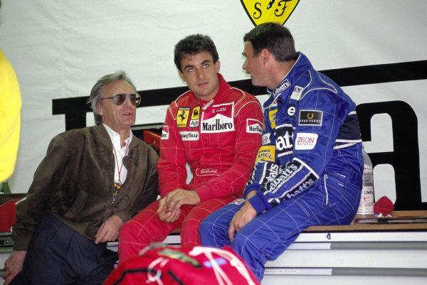 Bernie Ecclestone, Jean Alesi, Ferrari, and Nigel Mansell, Williams, talk in the Ferrari garage.