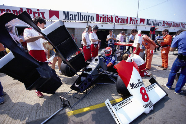 Niki Lauda, McLaren MP4-2 TAG, waits in the pits as mechanics move bodywork.