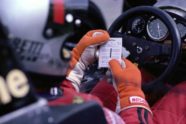 Mario Andretti studies measurements of his tyre pressures.