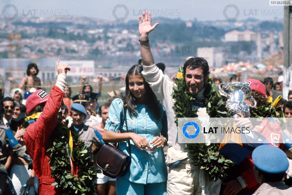 Interlagos, Sao Paulo, Brazil.24-26 January 1975.Carlos Pace (Brabham Ford) 1st position, celebrates winning his home Grand Prix, taking his maiden and only win. Emerson Fittipaldi, 2nd position and Jochen Mass, 3rd position (both McLaren Ford) also on the podium. Portrait.World Copyright - LAT Photographic