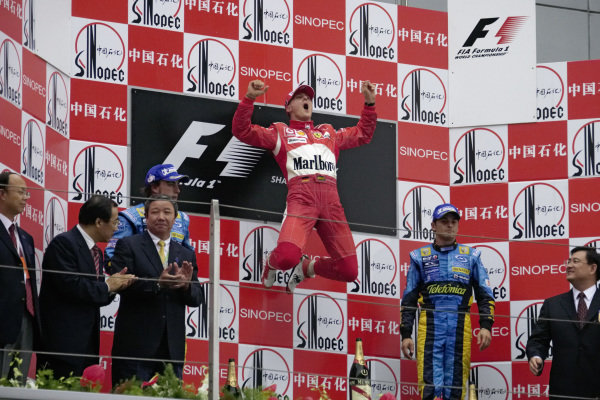Michael Schumacher's signature leap on the top step of the podium. Fernando Alonso, 2nd position, and Giancarlo Fisichella, 3rd position, stand either side.