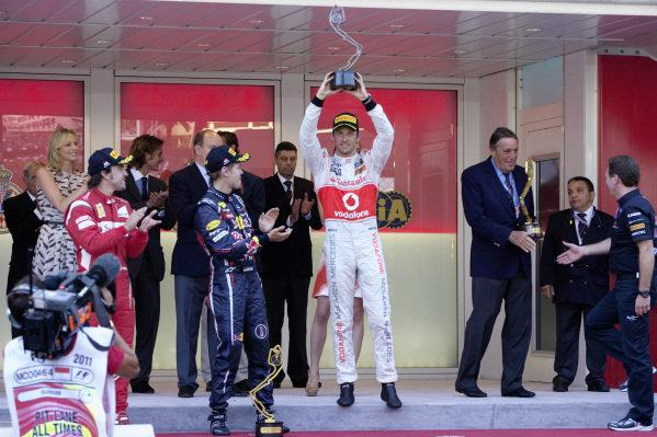 Jenson Button, 3rd position, celebrates on the podium alongside Sebastian Vettel, 1st position, and Fernando Alonso, 2nd position.