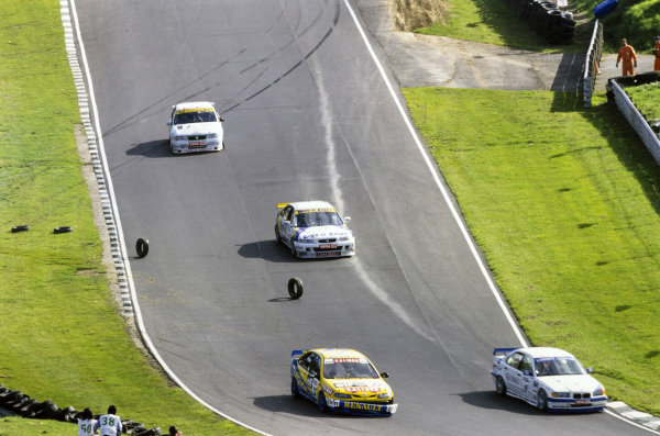 Colin Gallie, Team DCRS, BMW 320i, passes Jason Plato, Williams Renault Dealer Racing, Renault Laguna, who has damage to the front of his car, while behind Robb Gravett, Rock-it Cargo, Honda Accord, and Jamie Wall, Mint Motorsport, Vauxhall Cavalier, take avoiding action as some loose tyres roll across the track.