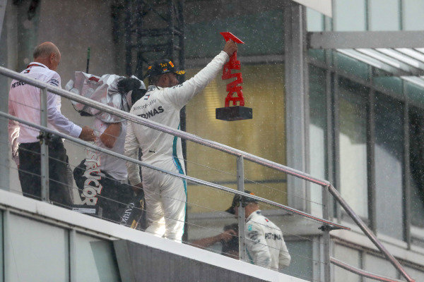 Lewis Hamilton, Mercedes AMG F1, raises his trophy on the podium.