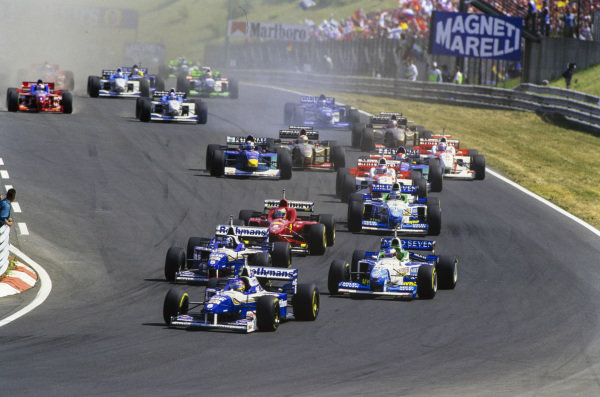 Jacques Villeneuve, Williams FW18 Renault, leads Jean Alesi, Benetton B196 Renault, Damon Hill, Williams FW18 Renault, Gerhard Berger, Benetton B196 Renault, and the rest of the field at the start of the race.