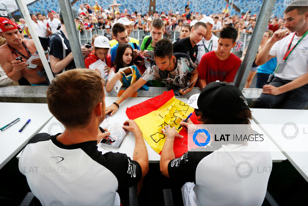 Hungaroring, Budapest, Hungary. Thursday 23 July 2015. Jenson Button, McLaren, and Fernando Alonso, McLaren, sign autographs for fans. World Copyright: Charles Coates/LAT Photographic ref: Digital Image _N7T1962