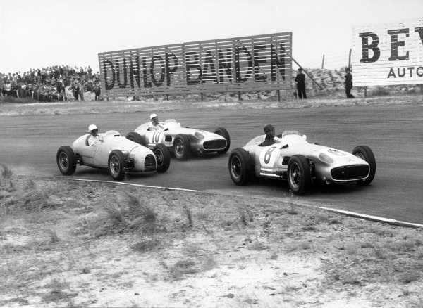 Zandvoort, Holland. 19th June 1955.Juan Manuel Fangio (Mercedes-Benz W196),1st position and Stirling Moss (Mercedes-Benz W196), 2nd position, pass Robert Manzon (Gordini 16), retired, action.World Copyright: LAT Photographic.Ref: 304 - 24.