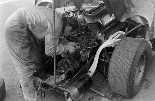 Mechanics work on a Ferrari engine in the pits.