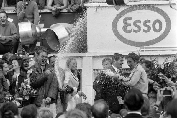 A.J. Foyt, 1st position, and 2.0 class winner Jo Siffert spray Champagne on the podium.