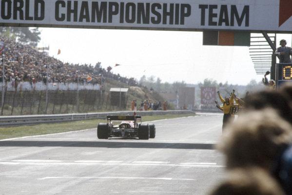 Michele Alboreto, Ferrari 126C4, crosses the finish line in celebration. The Ferrari team celebrate on the track.
