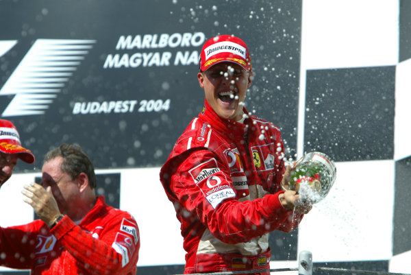 2004 Hungarian Grand Prix-Sunday Race,Hungaroring, Hungary.15th August 2004.Michael Schumacher, Ferrari F2004, on the podium.World Copyright LAT Photographic/Michael Cooper.Digital Image only (a high res version is available on request).