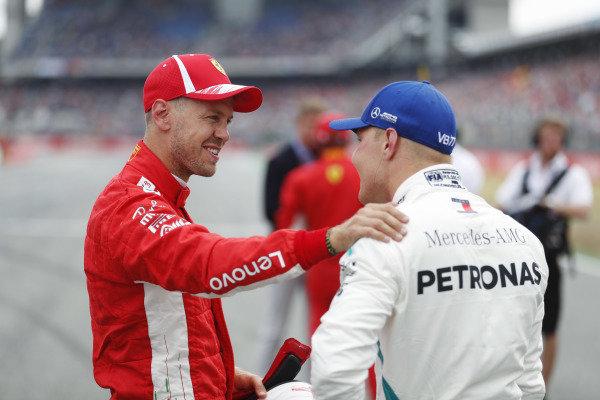 Sebastian Vettel, Ferrari, celebrates taking pole position, with Valtteri Bottas, Mercedes AMG F1.