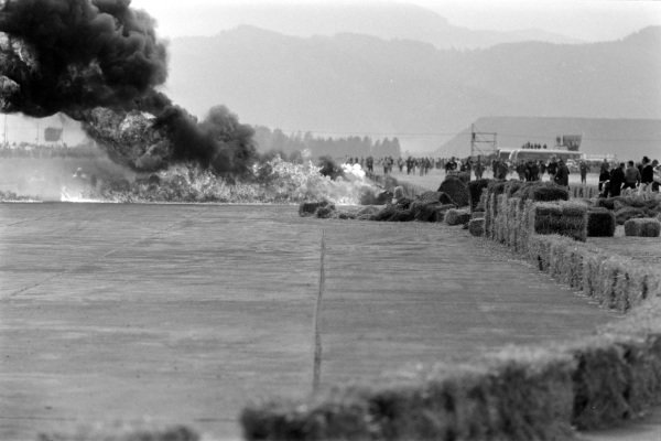 The car of Phil Hill, Cooper T66 Climax, crashes out and catches fire as Marshals attempt to contain the blaze.