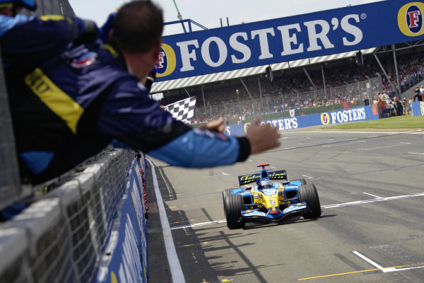Fernando Alonso, Renault R26 takes he chequered flag for victory as his team celebrate on the pitwall.