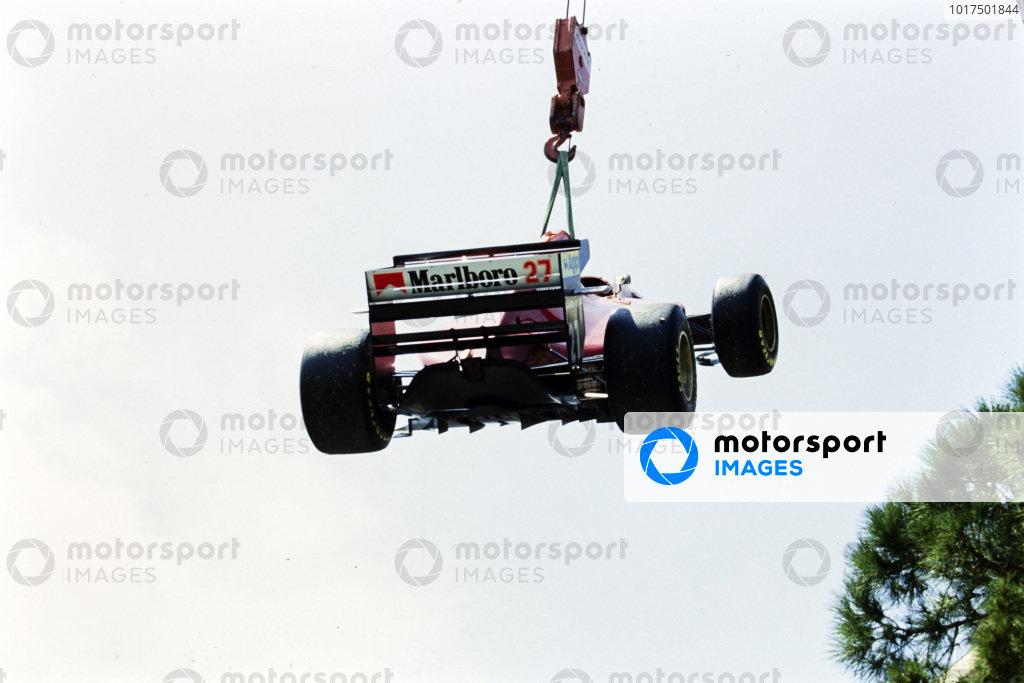 Jean Alesi's Ferrari 412T1 is craned away.