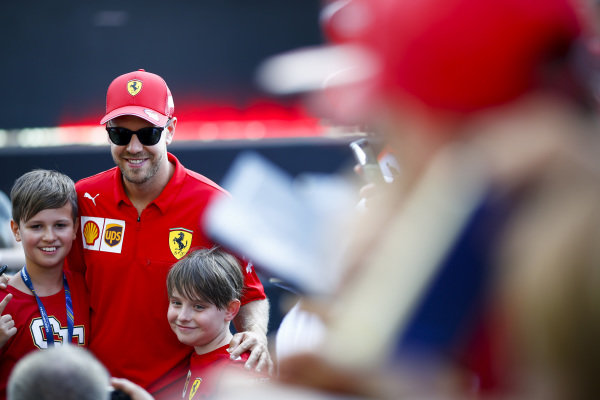 Sebastian Vettel, Ferrari poses for a photograph with young fans
