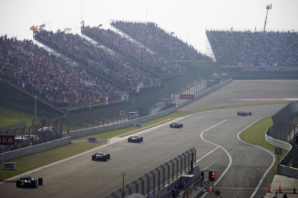 The field head into the first corner in front of packed grandstands.