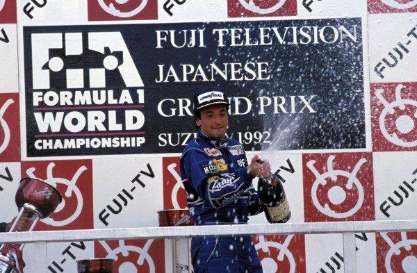 Riccardo Patrese, 1st position, sprays champagne on the podium.