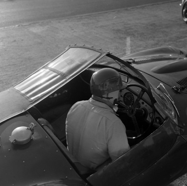 A driver sits in his car in the pits.