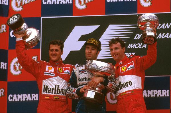 Imola, San Marino.25-27 APRIL 1997.Heinz-Harald Frentzen (Williams Renault) celebrates taking his maiden F1 win on the podium, with Michael Schumacher ( Ferrari) 2nd and Eddie Irvine (Ferrari) 3rd.Ref-97 SM 09.World  Copyright - LAT Photographic