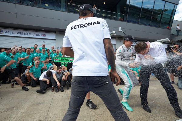 Red Bull Ring, Spielberg, Austria. Sunday 22 June 2014. Lewis Hamilton, Mercedes AMG, 2nd Position, Nico Rosberg, Mercedes AMG, 1st Position, and the Mercedes AMG team celebrate with Champagne. World Copyright: Steve Etherington/LAT Photographic. ref: Digital Image SNE26773copy