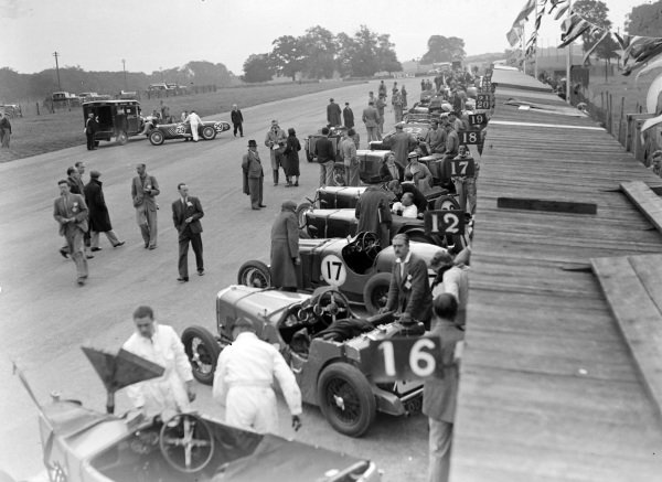 Competitors' cars are prepared while lined up along the pits.