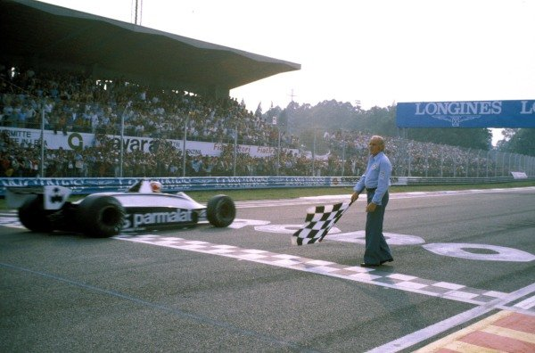 Nelson Piquet, Brabham BT49 Ford, takes the chequered flag at the finish at Imola