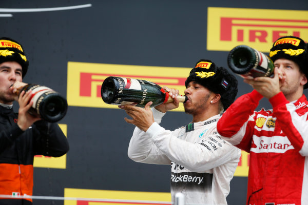 Sochi Autodrom, Sochi, Russia. Sunday 11 October 2015. Sergio Perez, Force India, 3rd Position, Lewis Hamilton, Mercedes AMG, 1st Position, and Sebastian Vettel, Ferrari, 2nd Position, taste the Champagne on the podium. World Copyright: Glenn Dunbar/LAT Photographic ref: Digital Image _89P2883