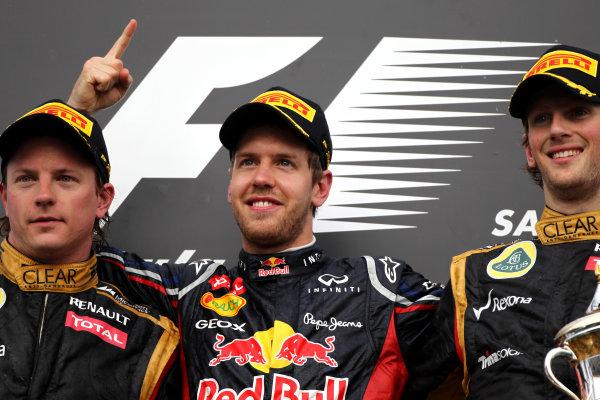 Bahrain International Circuit, Sakhir, Bahrain22nd April 2012Kimi Raikkonen, Lotus GP, 2nd position, Sebastian Vettel, Red Bull Racing, 1st position, and Romain Grosjean, Lotus GP, 3rd position, World Copyright: Andy Hone/LAT Photographicref: Digital Image HONY8738