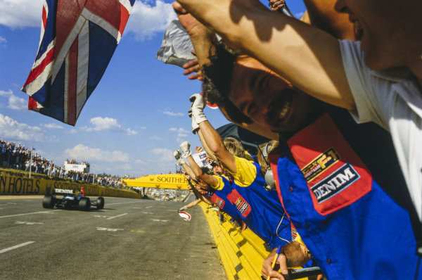 Williams mechanics celebrate as Nigel Mansell, Williams FW10 Honda, crosses the finish line.