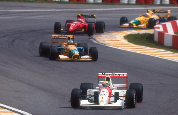 1992 Brazilian Grand Prix.Interlagos, Sao Paulo, Brazil.3-5 April 1992.Ayrton Senna (McLaren MP4/7A Honda) followed by Michael Schumacher (Benetton B191B Ford), Jean Alesi (Ferrari F92A) and Martin Brundle (Benetton B191B Ford) early on in the race.Ref-92 BRA 09.World Copyright - LAT Photographic
