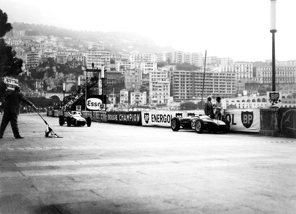 1960 Monaco Grand Prix.Monte Carlo, Monaco.26-29 May 1960.Stirling Moss (Lotus 18 Climax) takes the chequered flag for 1st position. On the right hand side Innes Ireland (Team Lotus) has a chat after retiring on the track side.World Copyright - LAT Photographic