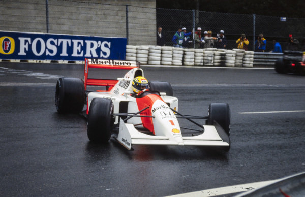 Ayrton Senna, McLaren MP4-7A Honda, with slick tyres on a wet track, recovers from a spin exiting La Source.