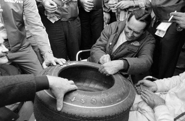Jack Brabham signs a Firestone tyre.