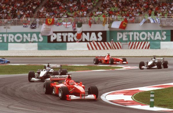 Sepang, Kuala Lumpur, Malaysia.20-22 October 2000.Michael Schumacher (Ferrari F1-2000) leads Mika Hakkinen, David Coulthard (both McLaren MP4/15 Mercedes) and Rubens Barrichello (Ferrari F1-2000). Ref-35mm A08.World Copyright - Tee/LAT Photographic