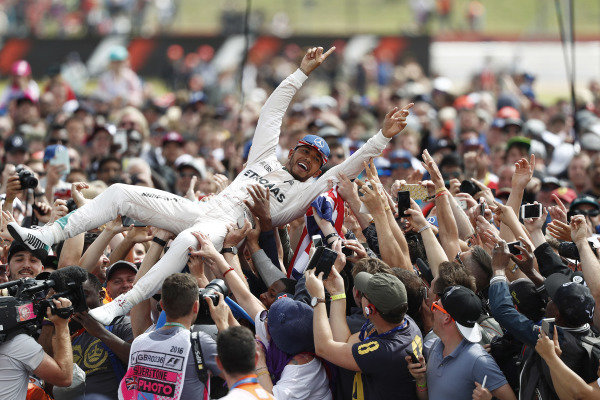 Lewis Hamilton, 1st position, celebrates with his home fans as they give him a crowd surf.