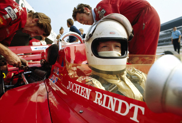 Jochen Rindt sits in his Lotus 72C Ford whilst mechanics work on the engine.