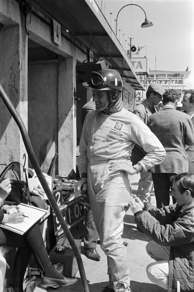 Jackie Stewart assists Graham Hill with repairs to his racesuit.